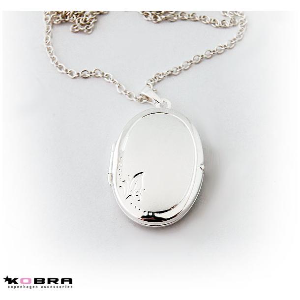 Oval sølv medaljon, matteret med blomst i siden
